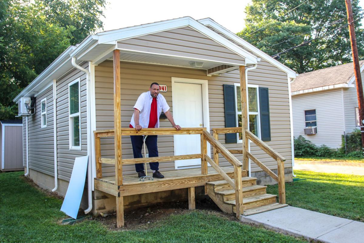 Brian Holland stands on the porch of his new home.